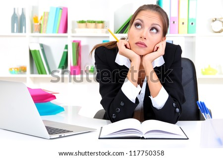 Thoughtful business woman with documents and notebook in office