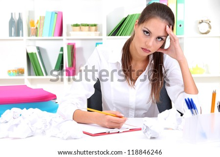 Thoughtful business woman with documents in office - stock photo