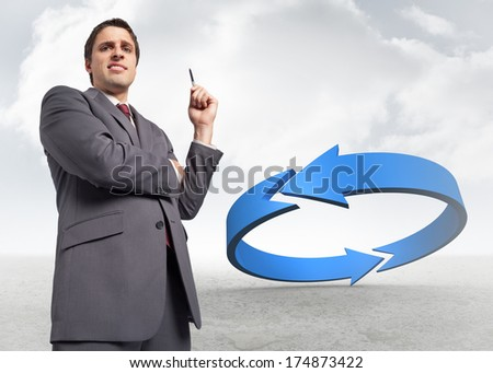 Thoughtful businessman holding pen against blue arrow in a desert landscape