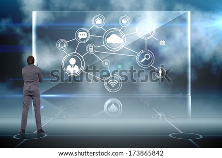 Thoughtful businessman holding pen against doorway on technological black background