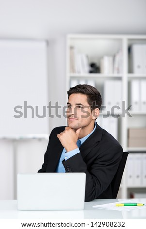 Thoughtful businessman in the office sitting at his desk behind his laptop with his chin resting on his hand staring off to the left in contemplation - stock photo