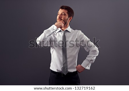 thoughtful businessman in white shirt over dark background