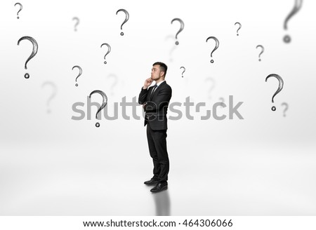 Thoughtful businessman looking upwards surrounded by question marks on white background. Ideas and concepts. Problems and decisions. Business staff.