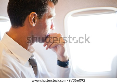 thoughtful businessman on airplane looking outside - stock photo