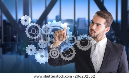Thoughtful businessman pointing something with his finger against room with large window looking on city - stock photo