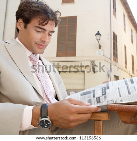 Thoughtful businessman reading the classified section of a newspaper while sitting at a coffee shop terrace, outdoors. - stock photo