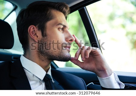 Thoughtful businessman riding in car - stock photo