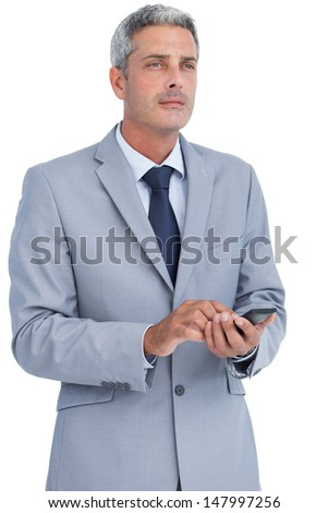 Thoughtful businessman sending text message against white background - stock photo