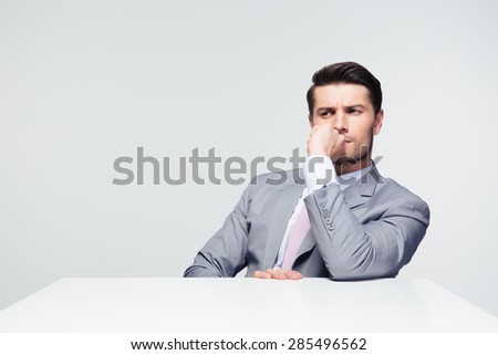 Thoughtful businessman sitting at the table over gray background and looking away - stock photo