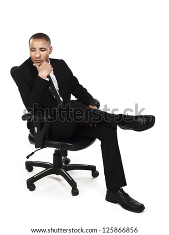 Thoughtful businessman sitting on chair with hand on chin against white background