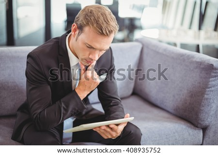 Thoughtful businessman sitting on sofa and looking at digital tablet in office - stock photo