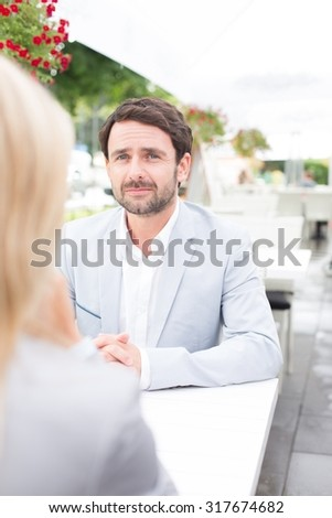 Thoughtful businessman sitting with female colleague at sidewalk cafe - stock photo