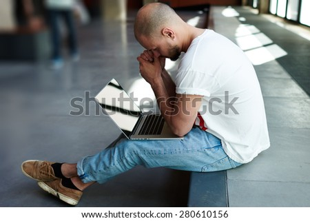 Thoughtful businessman sitting with open laptop computer looking frustrated, male freelancer with notebook sitting in modern space hall looking pensive and worried while thinking about planning - stock photo