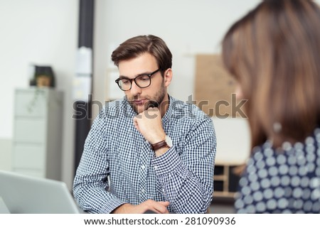 Thoughtful businessman studying his laptop with his chin on his hand as he works alongside a female colleague, view over her shoulder of his face - stock photo