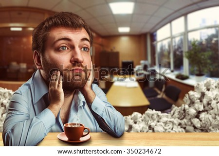 Thoughtful businessman with a big head drinking coffee in the office
