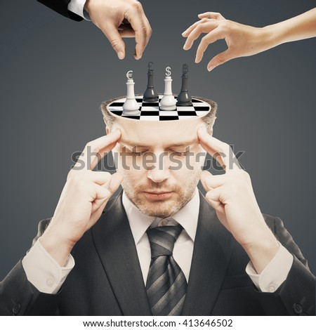Thoughtful businessman with chess board instead of brain and two businesspeople hands having a chess tournament with currency sign pawns on dark background - stock photo