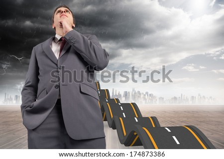 Thoughtful businessman with hand on chin against bumpy road leading to city