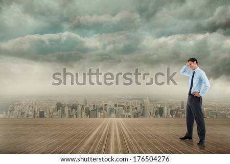 Thoughtful businessman with hand on head against cityscape on the horizon