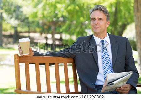Thoughtful businessman with newspaper and coffee cup sitting on park bench - stock photo