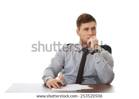 Thoughtful businessman writing a note in the office.