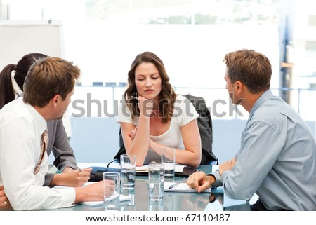 Thoughtful businesswoman at a table with her team during a meeting - stock photo