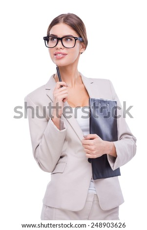 Thoughtful businesswoman. Confident young businesswoman holding clipboard and pen on chin while standing against white background - stock photo