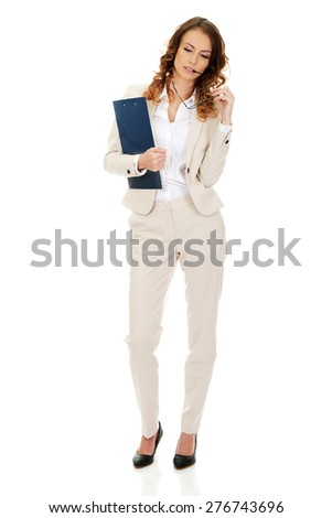 Thoughtful businesswoman holding a clipboard. - stock photo