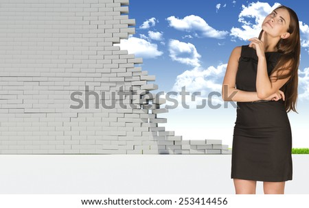 Thoughtful businesswoman in dress with crossed arms looking up. Dilapidated brick wall, green meadow and sky as backdrop. Concept of freedom - stock photo