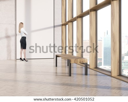Thoughtful businesswoman standing in interior with blank white banner and bench. 3D Rendering