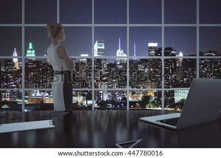 Thoughtful businesswoman standing in office with laptop, clipboard and other items on desktop. Illuminated night city view in the background. 3D Rendering - stock photo