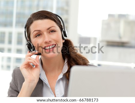 Thoughtful businesswoman talking on the phone while working on her computer at the office - stock photo