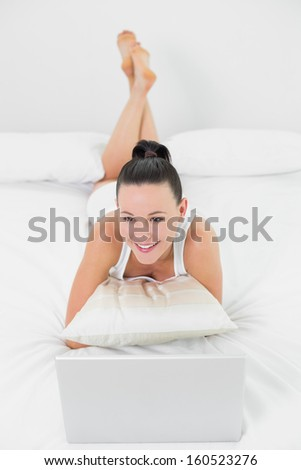 Thoughtful casual young woman with laptop lying in bed