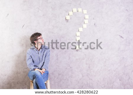 Thoughtful caucasian guy sitting next to and looking at sticker question mark glued onto concrete wall - stock photo
