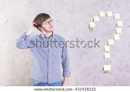 Thoughtful caucasian male standing next to sticker question mark glued onto concrete wall and scratching head - stock photo