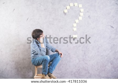 Thoughtful caucasian man sitting next to and looking at sticker question mark glued onto concrete wall - stock photo