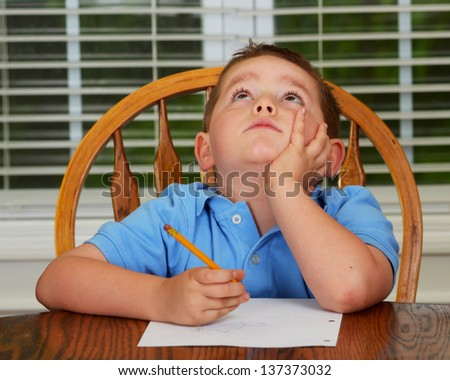Thoughtful child doing his homework at kitchen table at home - stock photo