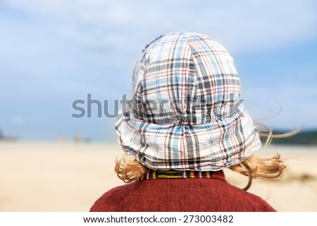 Thoughtful child looking into the infinity of the seascape, enjoying sun, sand and sea.  - stock photo