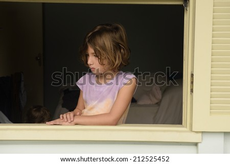 Thoughtful child looking out the window - stock photo