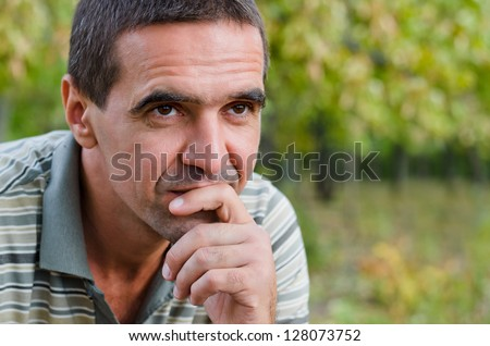 Thoughtful concerned good-looking mature man sitting outdoors against a green leafy background with his chin on his hand planning and thinking for the future - stock photo
