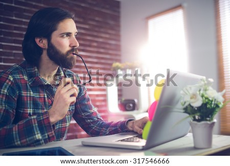 Thoughtful creative businessman with laptop working in office - stock photo
