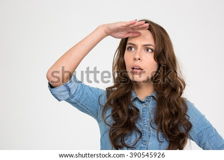 Thoughtful cute young woman with hand at her forehead looking far away over white background - stock photo
