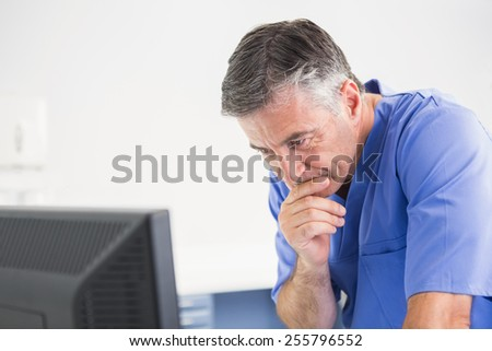 Thoughtful dentist using computer in dental clinic - stock photo