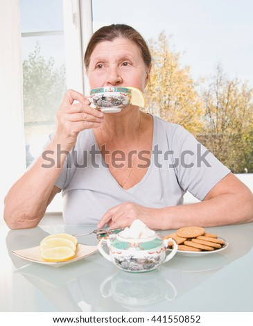Thoughtful elderly woman drinks tea with lemon. Studio photography in bright pastel colors. - stock photo