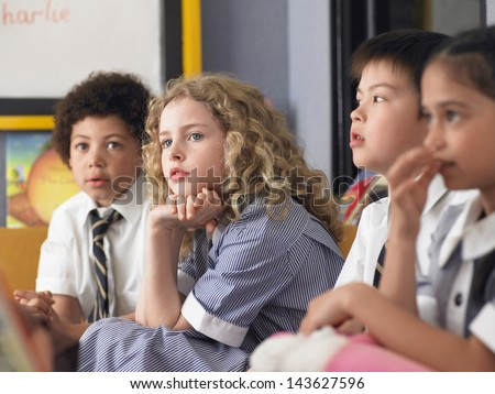 Thoughtful elementary students sitting in classroom - stock photo
