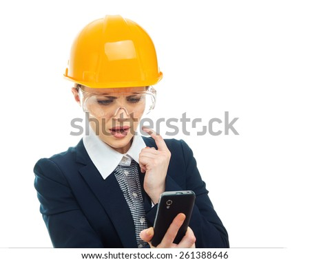 Thoughtful engineer woman with protective helmet looking her phone, isolated on white background.Close-up of female contractor or entrepreneur, studio-shot