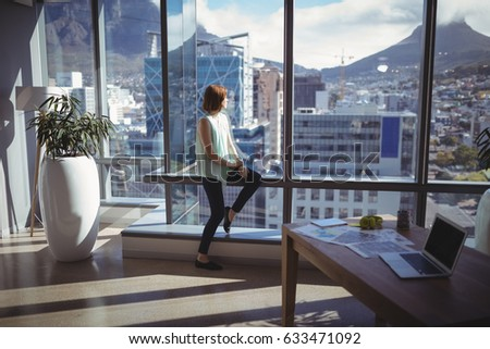 Thoughtful Executive Looking Through Window In Office