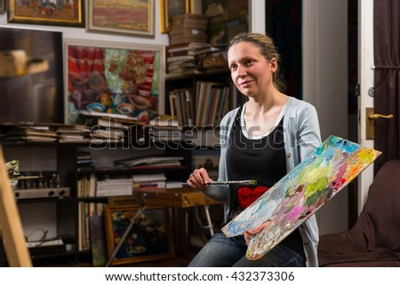 Thoughtful female artist  dreaming in her studio holding a colorful artists palette and paintbrush in her hand - stock photo