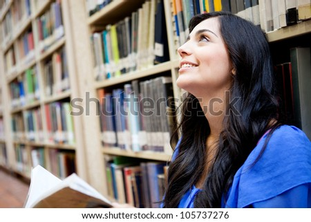 Thoughtful female student at the library holding a book