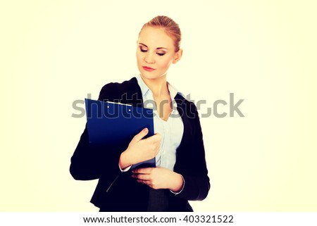 Thoughtful focused business woman holding clipboard - stock photo