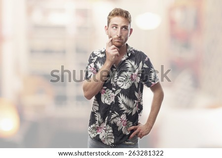 thoughtful ginger young man with hawaiian shirt - stock photo